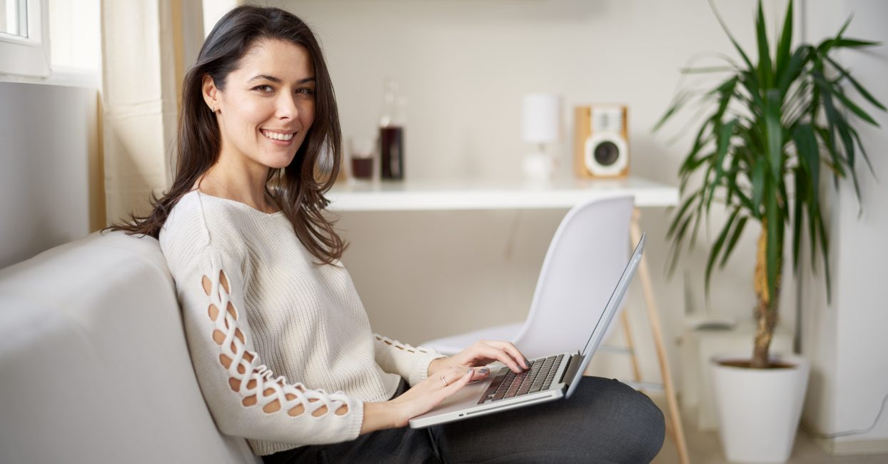Freelancer using laptop for searching internet while sitting on sofa in living room